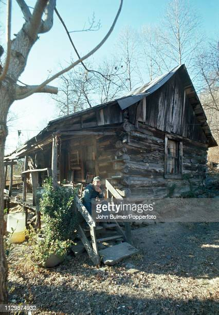 A man sitting on the stairs of the porch of his log house Pike County Kentucky US 1967