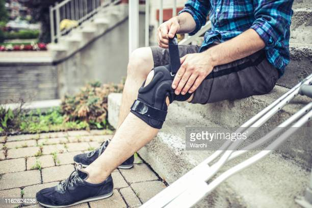 man sitting on the steps and adjusting his orthosis after having knee sprain - limb body part stock pictures, royalty-free photos & images