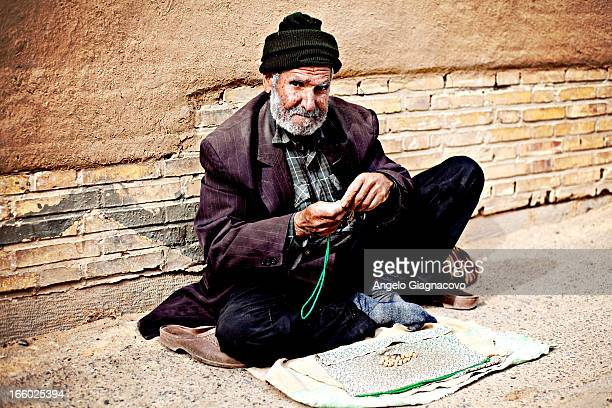 CONTENT] Man sitting on the street selling necklaces
