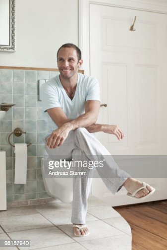 A Man Sitting On The Toilet In The Bathroom Stock Photo ...