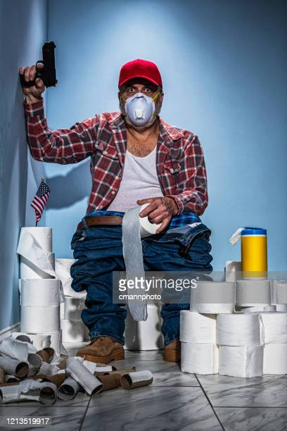 man sitting on toilet guarding his stash of toilet paper with a handgun - cloth face mask stock pictures, royalty-free photos & images