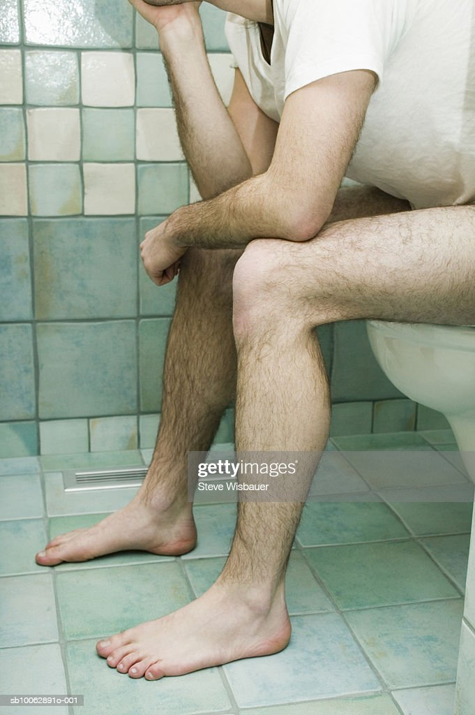 man with laptop sitting on the toilet - Talking