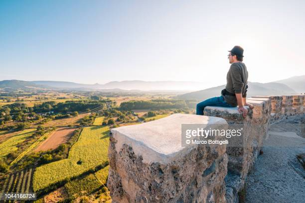 man sitting on top of a fortified wall looking at view - castle wall stock pictures, royalty-free photos & images