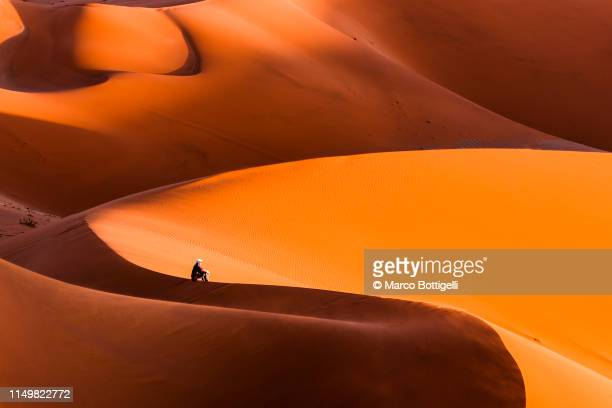 man sitting on top of a giant dune contemplating the sunset, namibia - namib naukluft national park stock pictures, royalty-free photos & images