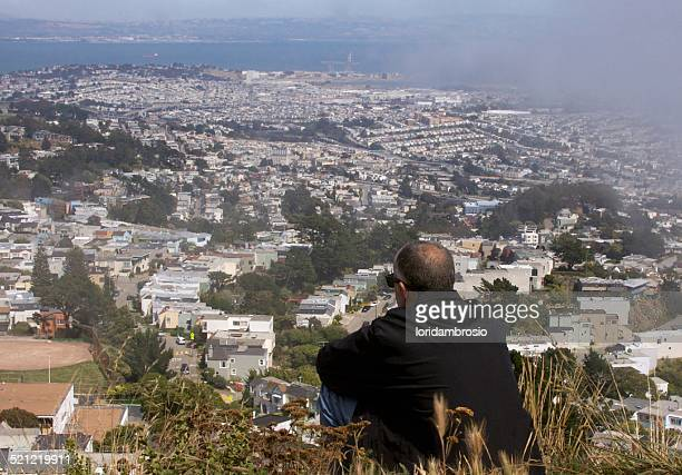 man sitting on top of a hill overlooking the city - east bay regional park stock pictures, royalty-free photos & images