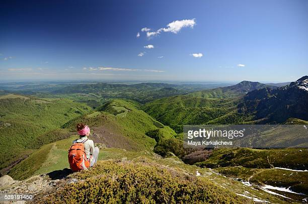 Man sitting on top of a mountain peak on a beautiful view