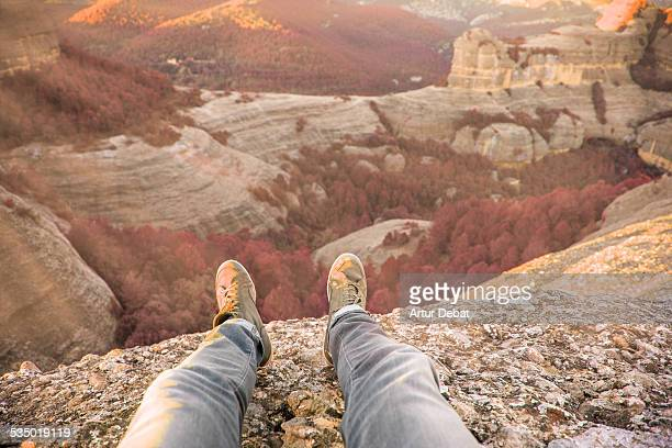 Man sitting on top of mountain from first POV