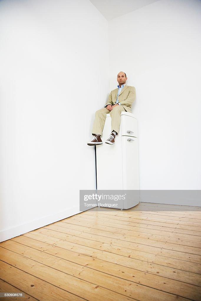 Man sitting on top of refrigerator stock photo getty images man sitting on top of refrigerator stock photo publicscrutiny Choice Image