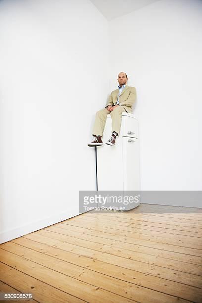 man sitting on top of refrigerator - frigo humour photos et images de collection