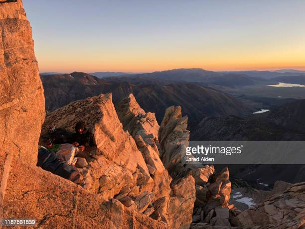 man sitting on top of the matterhorn peak during sunrise overlooking the sawtooth ridge traverse on the border of inyo national forest and yosemite national park near bridgeport california - pinnacle peak stock pictures, royalty-free photos & images