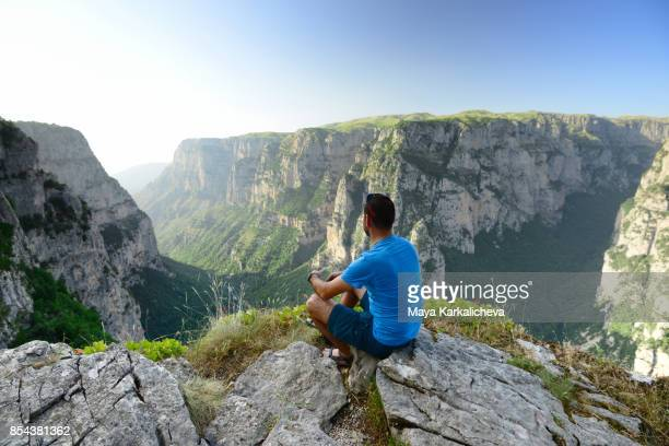 man sitting on top of vikos canyon, tymfi, zagoria / epirus, greece - epirus greece stock pictures, royalty-free photos & images