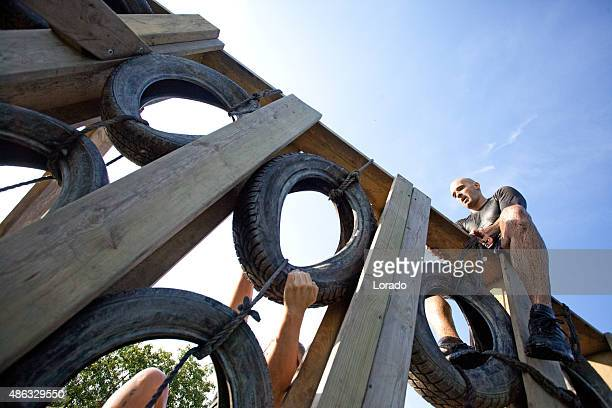 man sitting on top of wall of tires