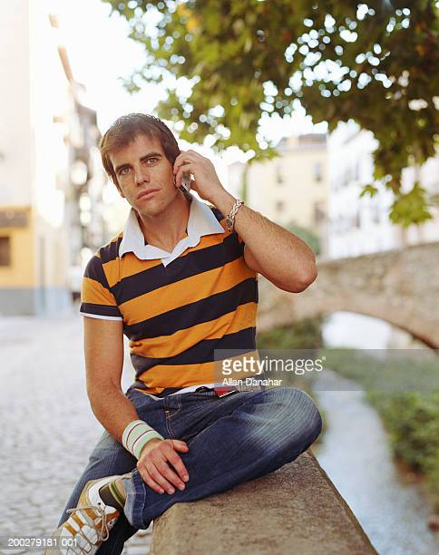 Man sitting on wall by river, using mobile phone