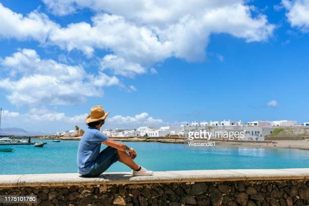 man sitting on wall looking towards caleta de sebo, la graciosa, canary islands, spain - islas canarias fotografías e imágenes de stock
