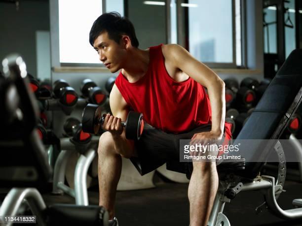 Man sitting on weight bench lifting dumb bells