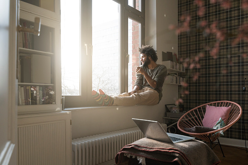 Man sitting on window sill in living room looking outside holding a cup - gettyimageskorea