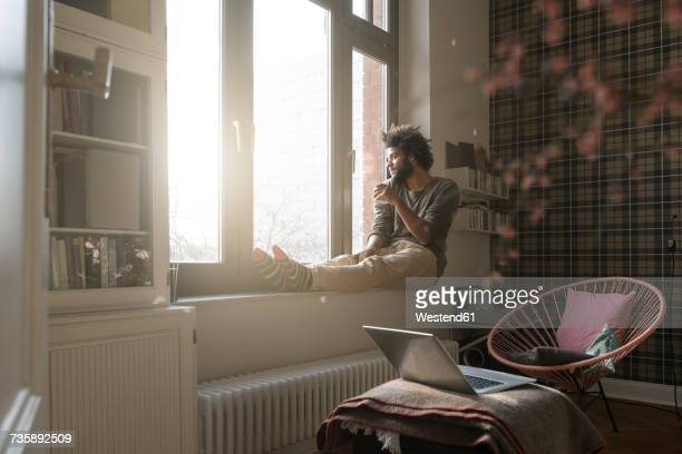 man sitting on window sill in living room looking outside holding a cup - cocoon stock pictures, royalty-free photos & images
