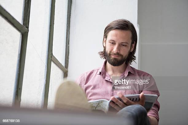 Man sitting on window sill reading magazine