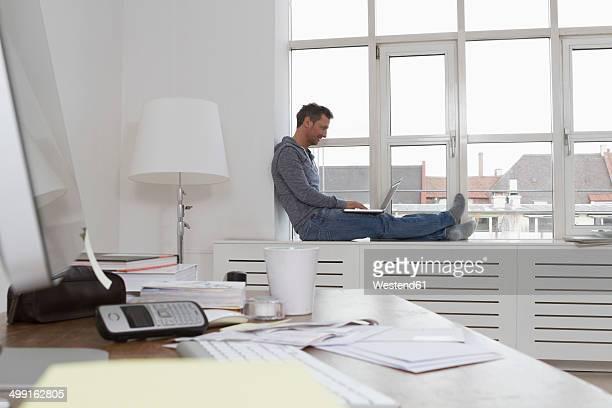 man sitting on windowsill using laptop - rebord de fenêtre photos et images de collection