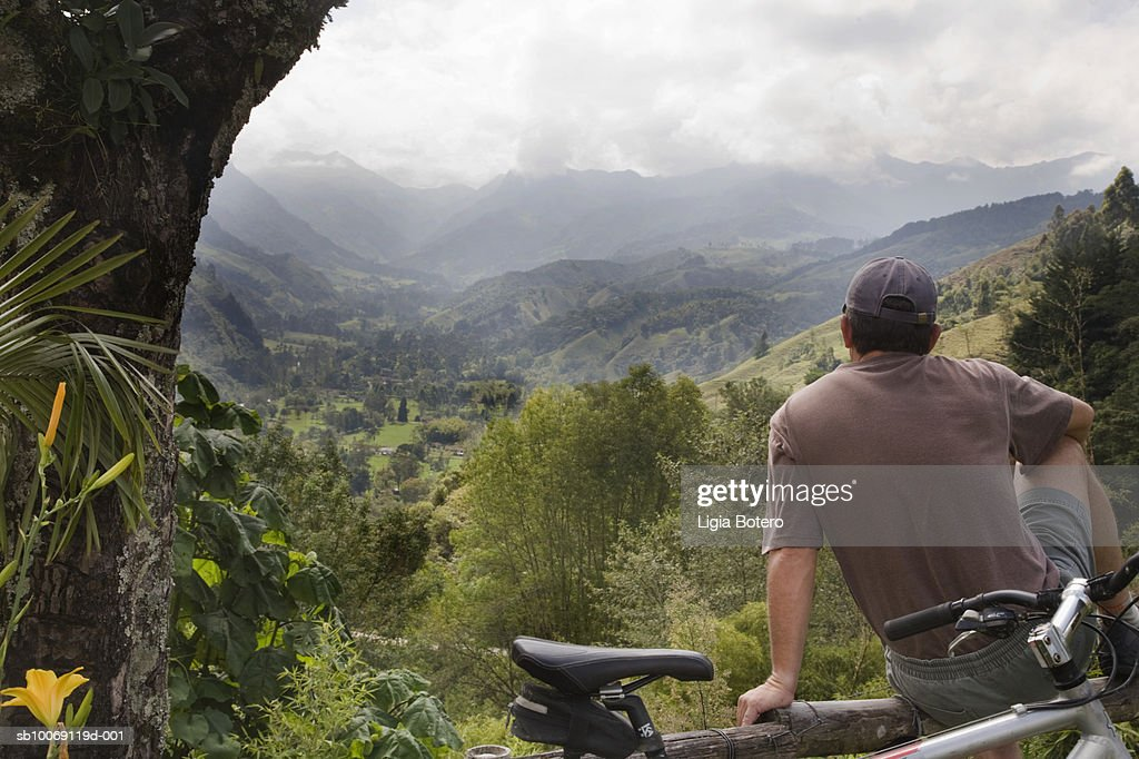 Man sitting on wood log, looking at view : Stockfoto