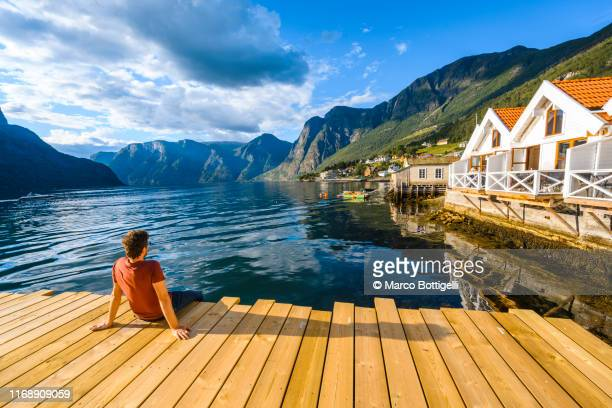 man sitting on wooden pier admiring a norwegian fjord, western norway - cultura norvegese foto e immagini stock