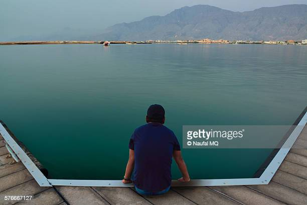man sitting on wooden pier by lake - ras al khaimah stock pictures, royalty-free photos & images