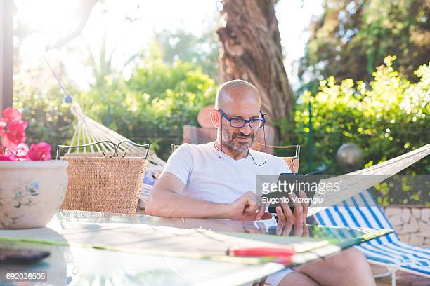 Man sitting outdoors at table using smartphone