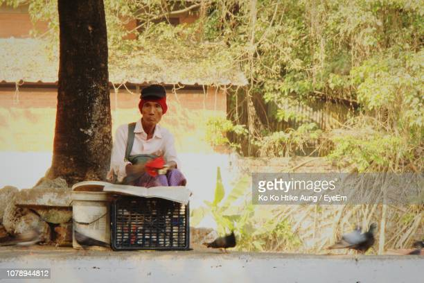 man sitting outdoors by tree - ko ko htike aung stock pictures, royalty-free photos & images