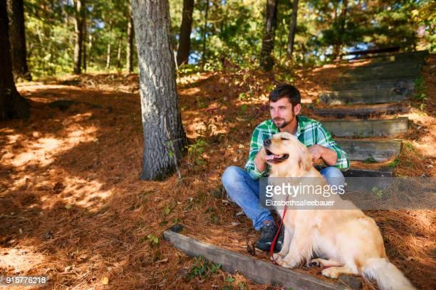 Man sitting outdoors, stroking a golden retriever dog