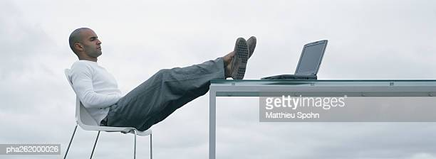 Man sitting outdoors with feet up on table and laptop on table, sideview