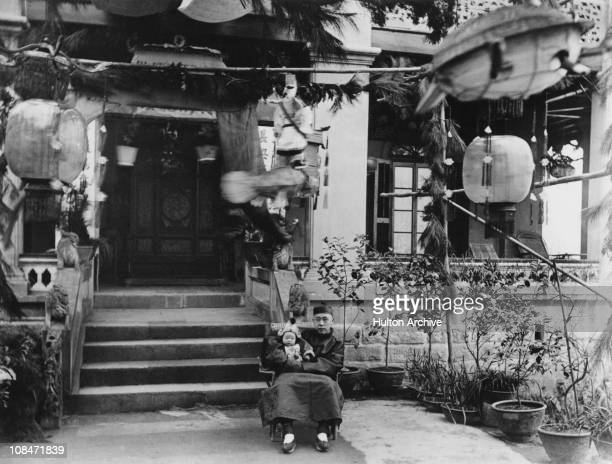 A man sitting outside a house in with a baby on his lap Nanjing China circa 1910