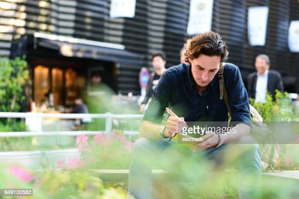 man sitting outside - authors stock photos and pictures