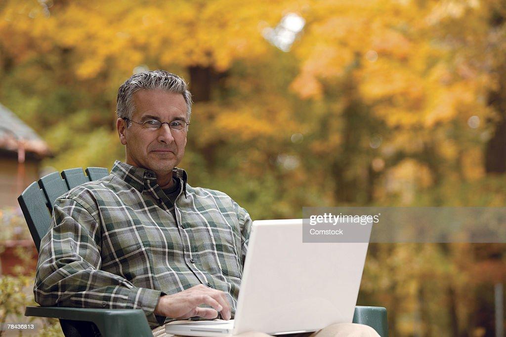 Man sitting outside using laptop computer : Stockfoto