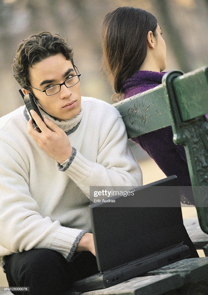 Man sitting outside with cell phone and laptop computer : Stockfoto