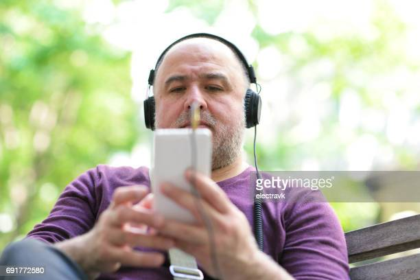 Man sitting outside with headphones on