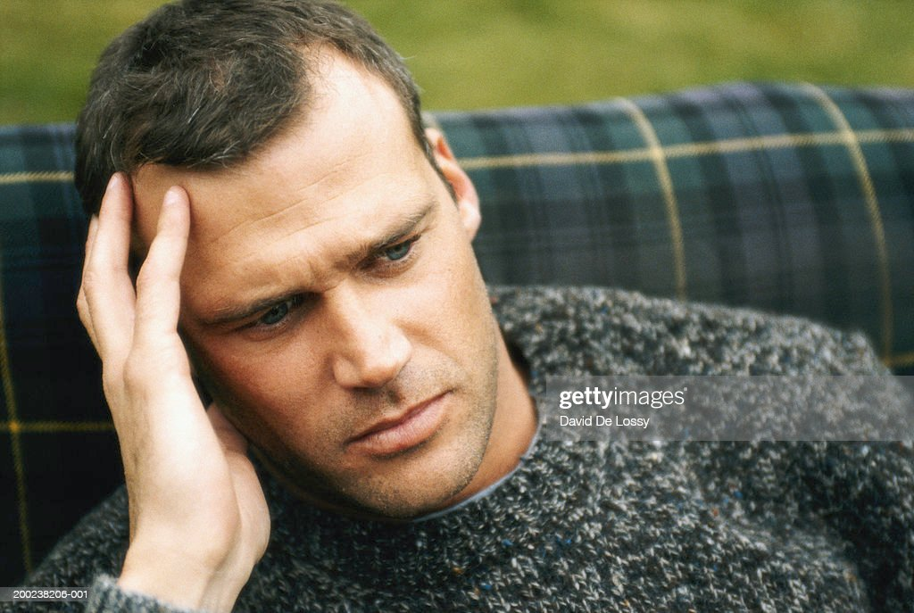 Man sitting pensively, close up : Stock Photo