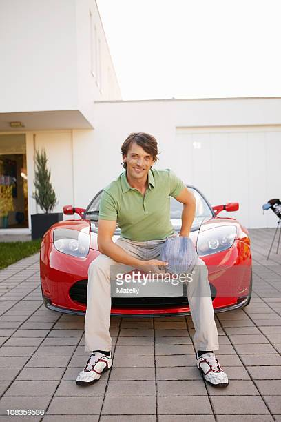 Man sitting proudly on his electric car