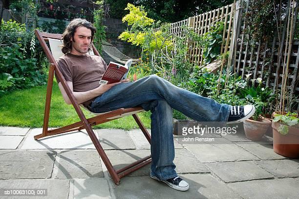 man sitting, reading in garden - 足を組む ストックフォトと画像