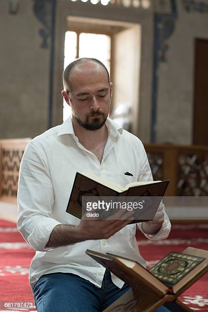 Man sitting reading Koran in mosque