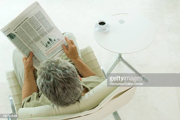 Man sitting, reading newspaper, high angle view