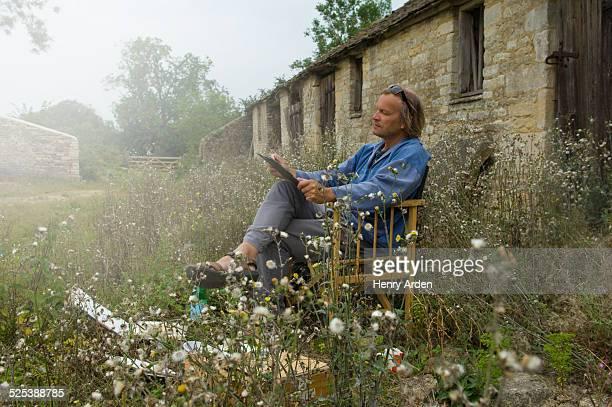 Man sitting sketching outside farm buildings