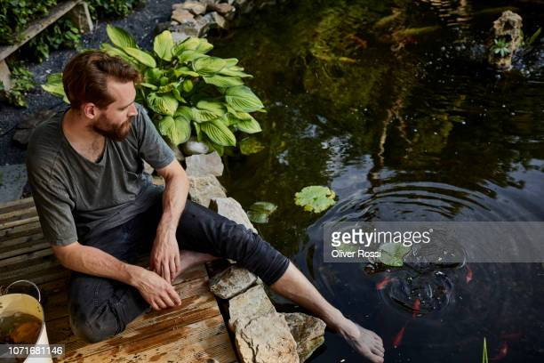 man sitting together at garden pond with foot in water - pequeno lago - fotografias e filmes do acervo