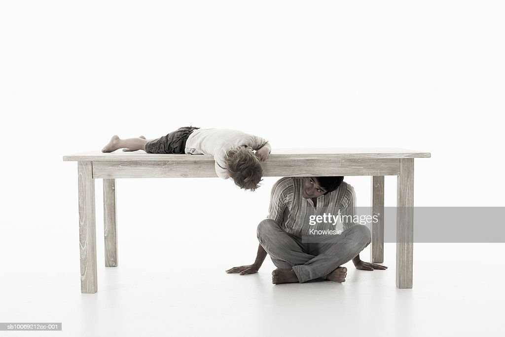 Man sitting under table playing with son (4-5 years), studio shot : Stockfoto