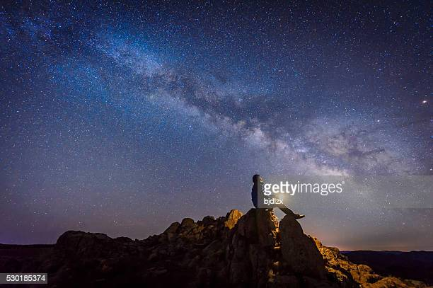 man sitting under the milky way galaxy - spiritualiteit stockfoto's en -beelden