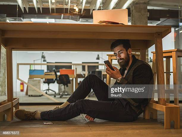 Man sitting under the table and using mobile phone.