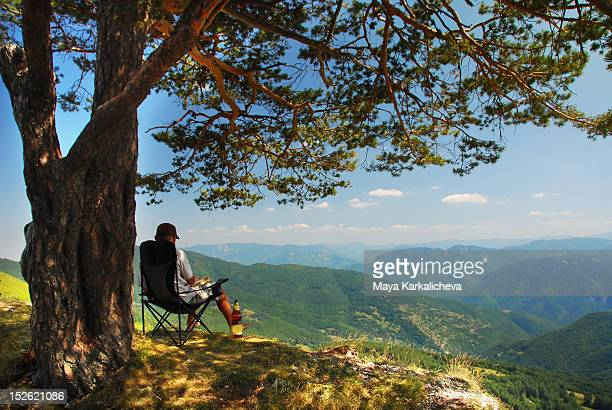 Man sitting under tree in front of mountains