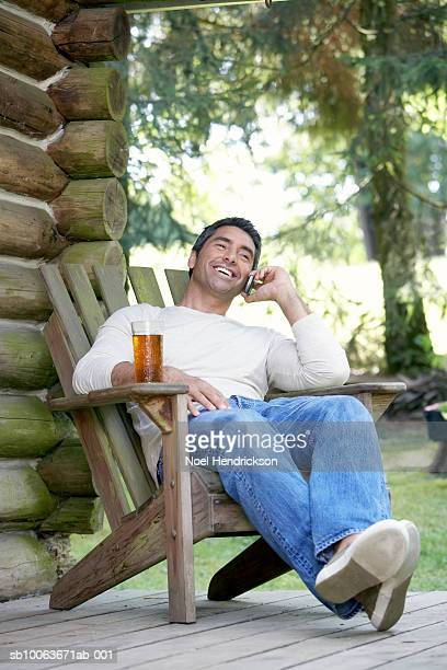 Man sitting using mobile phone on porch