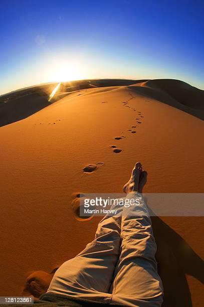 Man sitting watching sunset in the sand dunes of Erg Chebbi area, Sahara desert, Morocco, North Africa