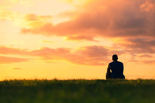 Man sitting watching sunset 944915072
