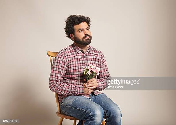 A man sitting with a bunch of pink carnations